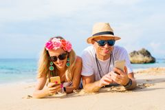 Couple using their phones on the beach. Hipster couple using their phones on the beach while lying on the beach Royalty Free Stock Images