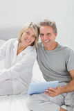 Couple using their tablet pc smiling at camera Stock Image