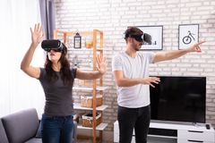 Couple Using Virtual Reality Device. Young Couple Using Virtual Reality Device At Home stock images