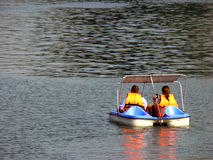 Couple On Vacation. A couple on vacation cruising a lake on a pedal boat stock images