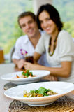 Couple On Vacation. A young couple on vacation eating lunch at a relaxed outdoor restaurant (focus on food Stock Photography