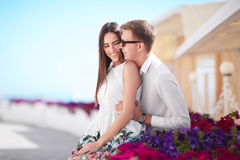A couple on a vacation. Beautiful lovers on a sunny shore background. An adorable girlfriend and a smiling boyfriend. A cheerful and romantic couple relaxing on Royalty Free Stock Photos