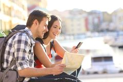 Couple on vacation booking hotel online. Happy couple on vacation booking hotel online with a smart phone Stock Images