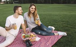 Couple on vacation. Cut view of couple whom has a small vacation and decided to go to park and sit there with some fruits and juice and just relax. Boy is Royalty Free Stock Photo