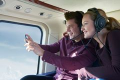 Couple On Vacation Taking Ride In Helicopter Stock Photo