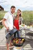 Couple on vacation having barbecue stock images