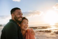 Couple on a vacation near the sea. Man holding his partner with his arm around her standing at a beach and looking away. Man and women enjoying vacation near the stock photos