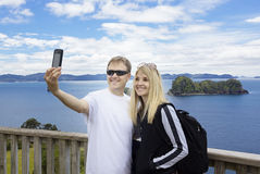Couple on vacation taking photo of beautiful ocean view Stock Images