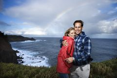 Couple vacationing in Maui, Hawaii. Caucasian mid-adult  couple embracing in front ocean with rainbow in background in Maui, Hawaii Stock Image