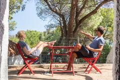 Couple on vacations resting in front of bungalow house at camping site in pure nature. Family vacation travel, holiday. Couple on vacations resting and enjoing royalty free stock photos