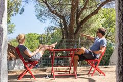 Couple on vacations resting in front of bungalow house at camping site in pure nature. Family vacation travel, holiday. Couple on vacations resting and enjoing royalty free stock photo
