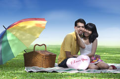Couple with valentine heart. Romentic young couple sitting in the park with pink valentine heart shape royalty free stock photos