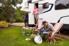 Couple In Van Enjoying Barbeque On Camping Holiday. Smiling royalty free stock images