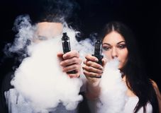 Young couple vaping e-cigarette with smoke on black closeup. Couple vaping. Unrecognizable young men and women in the clouds of smoke showing their vapes to royalty free stock photo