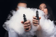 Young couple vaping e-cigarette with smoke on black closeup. Couple vaping. Unrecognizable young men and women in the clouds of smoke showing their vapes to royalty free stock images