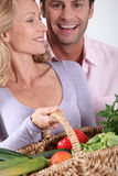 Couple with vegetable basket. Couple laughing with vegetable basket stock photo