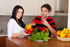 Couple with vegetables in kitchen Royalty Free Stock Images