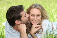 Couple very much in love. Affectionate couple alying in the park Royalty Free Stock Photography