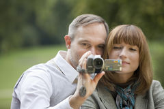 Couple with video camera filming Stock Photo