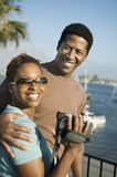 Couple with video camera at marina Stock Images