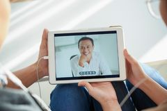Couple video chatting with man on tablet stock photo