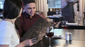 Couple view the restaurant menus stock video footage