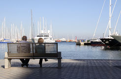 Couple viewing boats at harbor. A couple seated at a bench leisurely viewing the yachts, sailboats, boats coming and going in a harbor Stock Photo