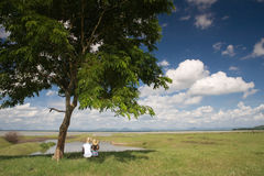 Couple viewing rural scenery. Two people sat under tree viewing beautiful countryside landscape Royalty Free Stock Image