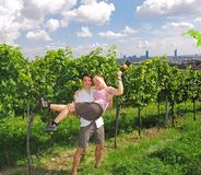 Couple in the vineyards. A young couple is enjoying its time together in the vineyards of Vienna. The city with its skyscrapers is in the background. Austria's royalty free stock photos