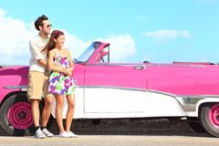 Couple and vintage retro car. Happy smiling young couple standing by pink old vintage car during summer road trip travel in Havana, Cuba. Interracial couple Royalty Free Stock Photos