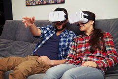 Couple in virtual reality glasses discussing something at home Royalty Free Stock Photography