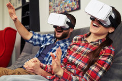 Couple in virtual reality glasses surprised by virtual reality h Stock Image