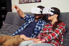 Couple in virtual reality glasses watching something and man sho Stock Images