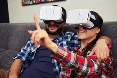 Couple in virtual reality glasses watching something and woman t Royalty Free Stock Images
