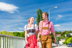 Couple visiting Bavarian fair having fun. Couple visiting together Bavarian fair in national costume leather pants and Dirndl Royalty Free Stock Photo