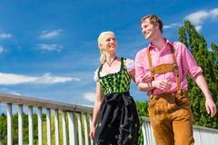 Couple visiting Bavarian fair having fun. Couple visiting together Bavarian fair in national costume leather pants and Dirndl Royalty Free Stock Image
