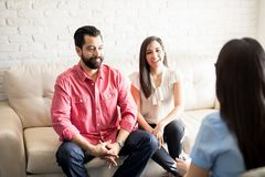 Couple visiting psychologist for consultation. Happy hispanic couple sitting on couch while consultation with psychologist, visiting relationship counselor for royalty free stock images