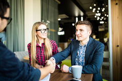 Couple visiting a realtor or manager. Men are shaking hands Stock Photo