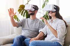 Couple in VR glasses holding hands and orienting in space Royalty Free Stock Photo