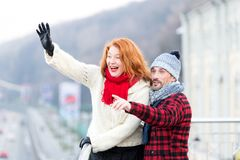 Couple wag to air. Red hair woman wag from the bridge. Happy lady with guy welcomes to friends. royalty free stock photography