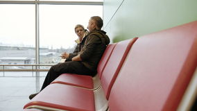 Couple waiting at airport terminal with tickets stock footage