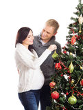 A couple waiting for the baby at Christmas near the tree. A young pregnant mother and a happy father decorating the Christmas tree. The image is isolated on a Stock Photos