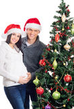 A couple waiting for the baby at Christmas near the tree Stock Photos