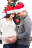 A couple waiting for the baby at Christmas near the tree. A young pregnant mother and a happy father decorating the Christmas tree. The image is isolated on a Royalty Free Stock Images