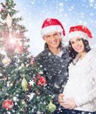 A couple waiting for the baby at Christmas near the tree Royalty Free Stock Images