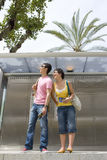 Couple waiting at bus station, smiling, low angle view Royalty Free Stock Photos