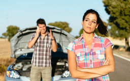 Couple waiting for car service after breakdown. Upset women waiting for car help while men arguing on the cellphone with insurance service. Couple in road trip Stock Photo