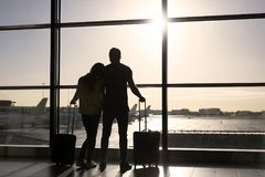 Couple waiting for flight in airport. Young couple waiting for flight in airport and looking forward royalty free stock photos