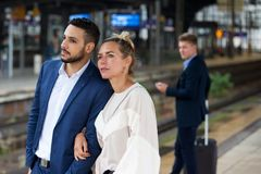 Couple waiting on platform at train station. And men in the background Royalty Free Stock Photography