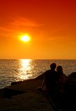 A couple waiting for sunset. Nice sunset, clear orange sky Stock Images